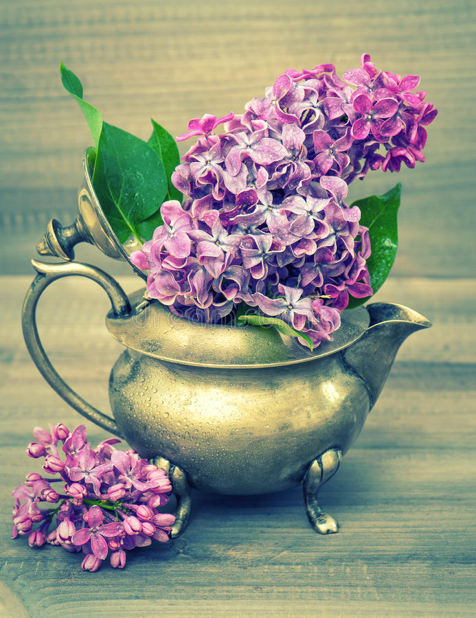 Lilac flowers bouquet on wooden background. Retro style royalty free stock photo