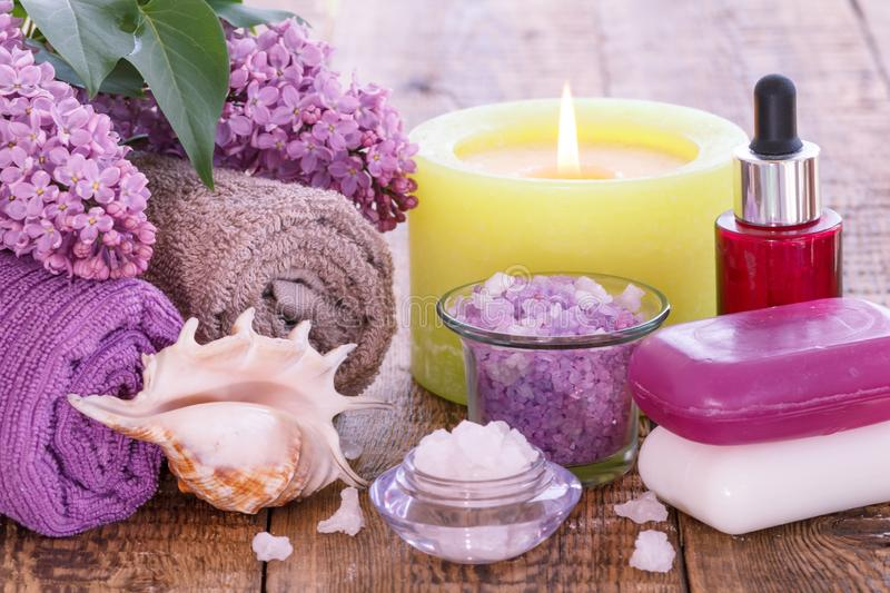 Lilac flowers, towels, red bottle with aromatic oil, burning candle, bowls with sea salt and soap. Lilac flowers with green leaves, towels for bathroom royalty free stock image
