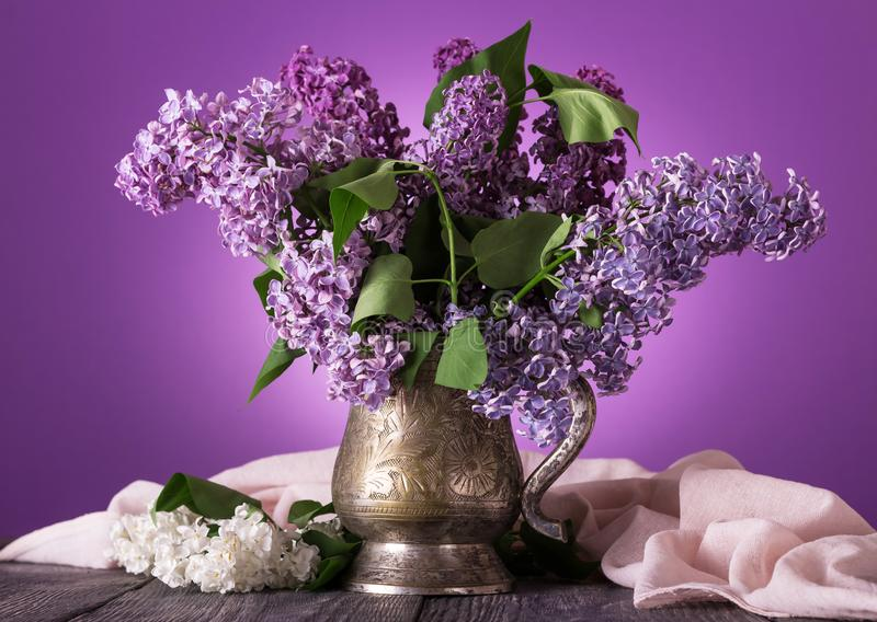Lilac flowers in an old vase, near sprig of white flowers on background of fine fabric stock photos