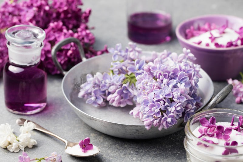 Lilac flowers sugar and syrup, essential oil with flower blossoms in glass jar Grey stone background.  stock photo
