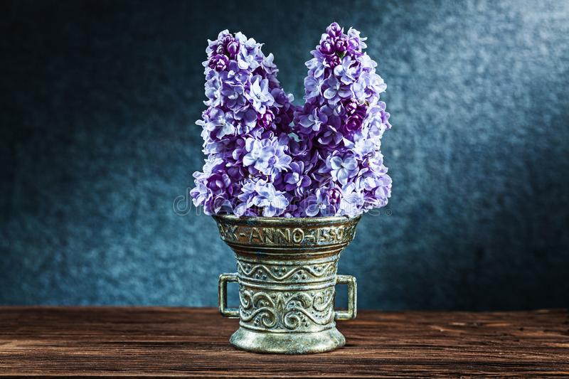 Lilac flowers in vintage bronze bowl on black background royalty free stock photo