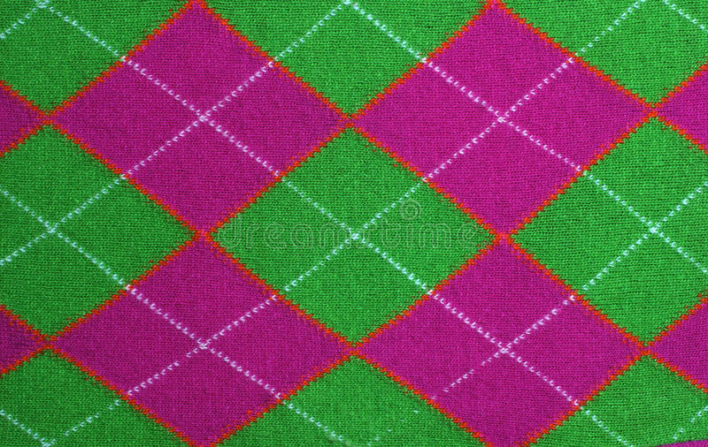 Lilac and green argyle pattern fabric. Woolen knitted lilac and green fabric with rhomboid argyle pattern background stock photos