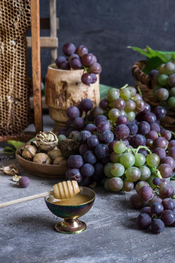 Lilac and green bunches of grapes and fresh sweet honey royalty free stock photography
