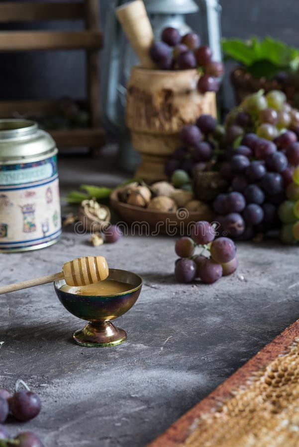 Lilac and green bunches of grapes and fresh sweet honey royalty free stock photo