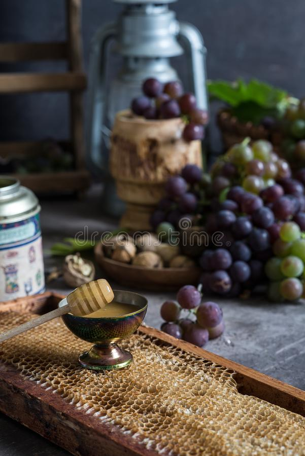 Lilac and green bunches of grapes and fresh sweet honey royalty free stock photos