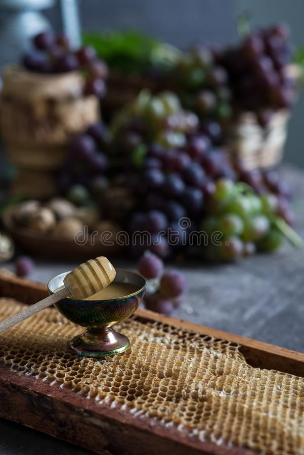 Lilac and green bunches of grapes and fresh sweet honey stock image