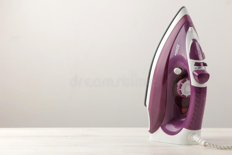 lilac iron on a light background. ironing clothes. household electrical appliances royalty free stock image