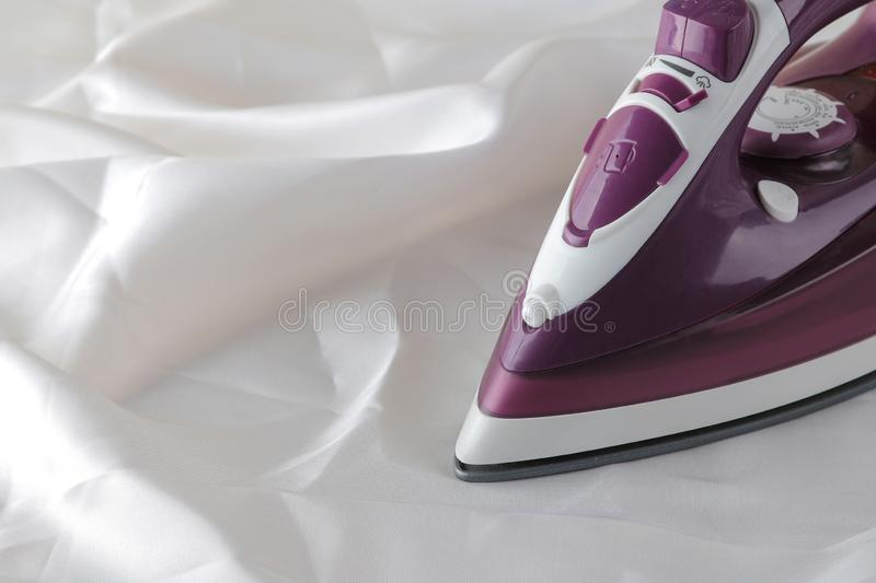Lilac iron on a piece of white crumpled fabric. ironing clothes. household electrical appliances royalty free stock photo