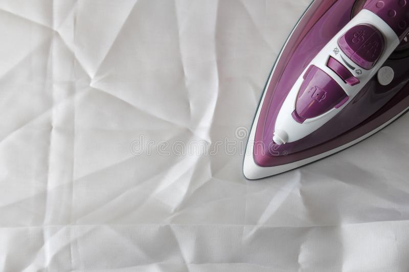 Lilac iron on a piece of white crumpled fabric. ironing clothes. household electrical appliances. view from above stock photo