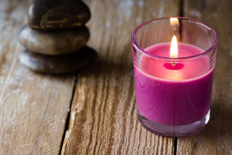 Lilac lavendelkaars en een stapel evenwichtige zen stenen op de achtergrond, op houten oppervlakte, copyspace voor tekst, harmoni stock foto's