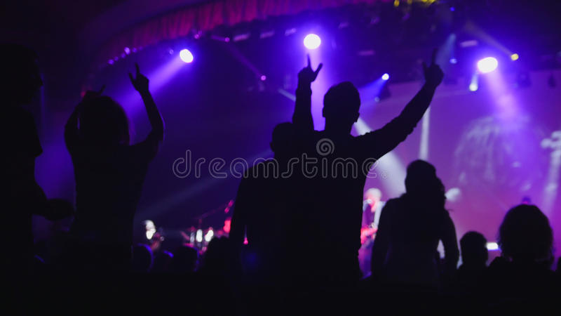 Lilac light on stage - a lot of people dancing at the concert stock image