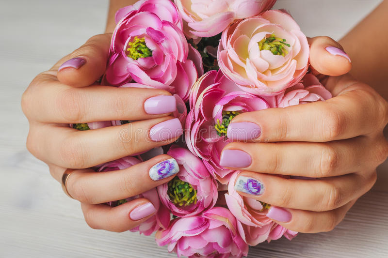 Lilac nail art with printed flowers on light background royalty free stock images
