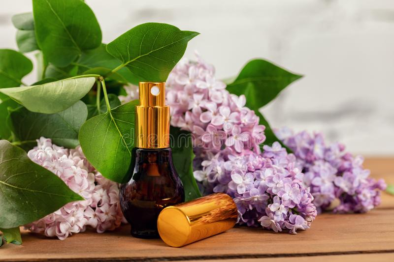 Lilac perfume - scent sprayer and blossoms on wooden table royalty free stock photo