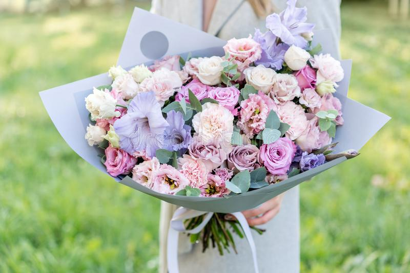 Lilac and pink pastel beautiful spring bouquet. Young girl holding a flower arrangement with various flowers. Bright. Dawn or sunset sun stock photography