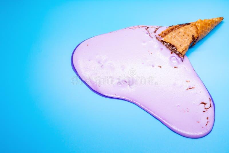 Lilac roomijskegel op blauwe achtergrond wordt gesmolten die stock foto