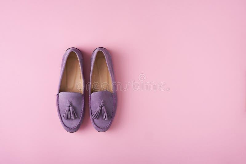 Lilac schoenen van suèdemocassins over lilac roze achtergrond stock fotografie