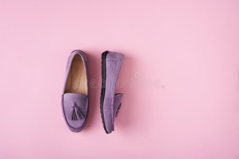 Lilac schoenen van suèdemocassins over lilac roze achtergrond royalty-vrije stock afbeeldingen