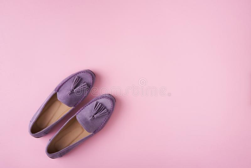 Lilac schoenen van suèdemocassins over lilac roze achtergrond stock foto