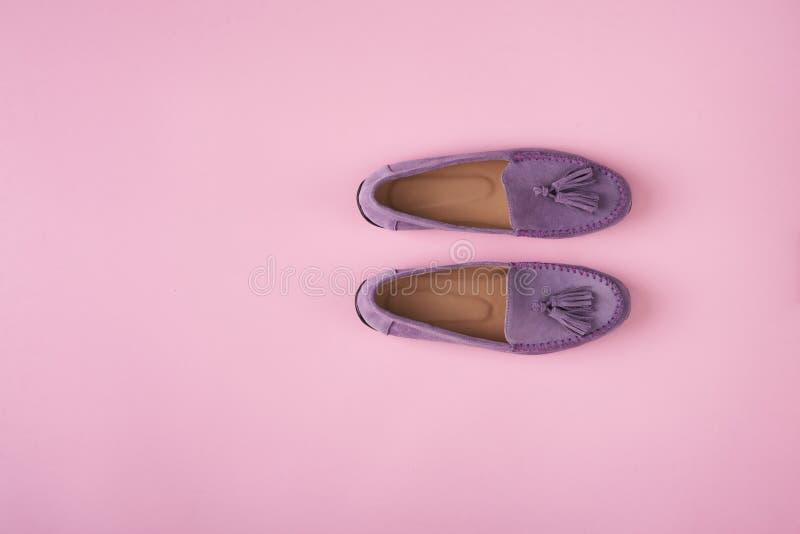 Lilac schoenen van suèdemocassins over lilac roze achtergrond royalty-vrije stock foto