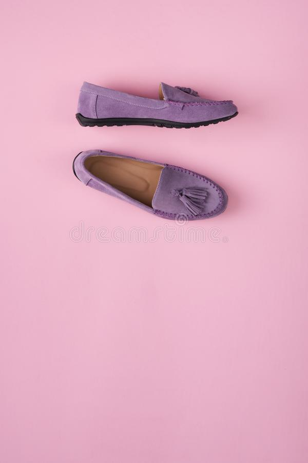 Lilac schoenen van suèdemocassins over lilac roze achtergrond stock foto's