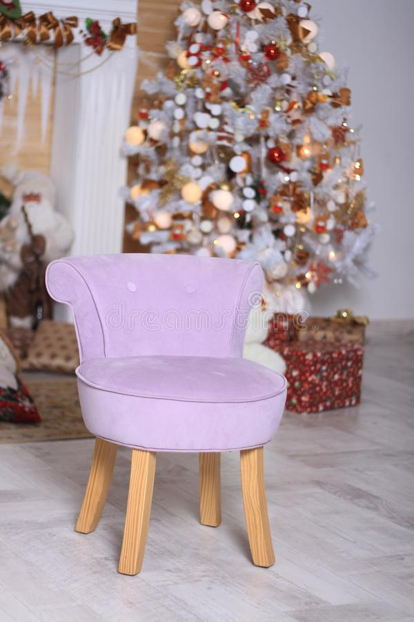 The lilac small chair costs. In studio against the background of a New Year tree and gifts stock photography
