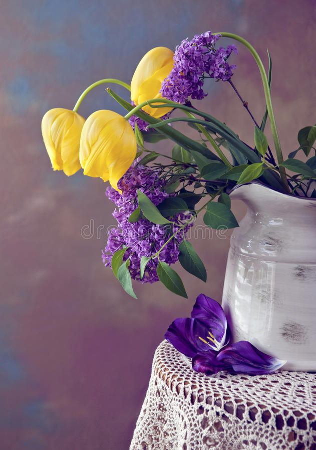 Lilac and Tulip Still life. A beautiful spring flower arrangement with yellow tulips and lilac in a vase, low light still life royalty free stock image