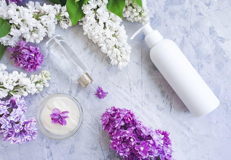Lilas cosmétique crème de fleur sur un fond concret gris, extrait photographie stock libre de droits