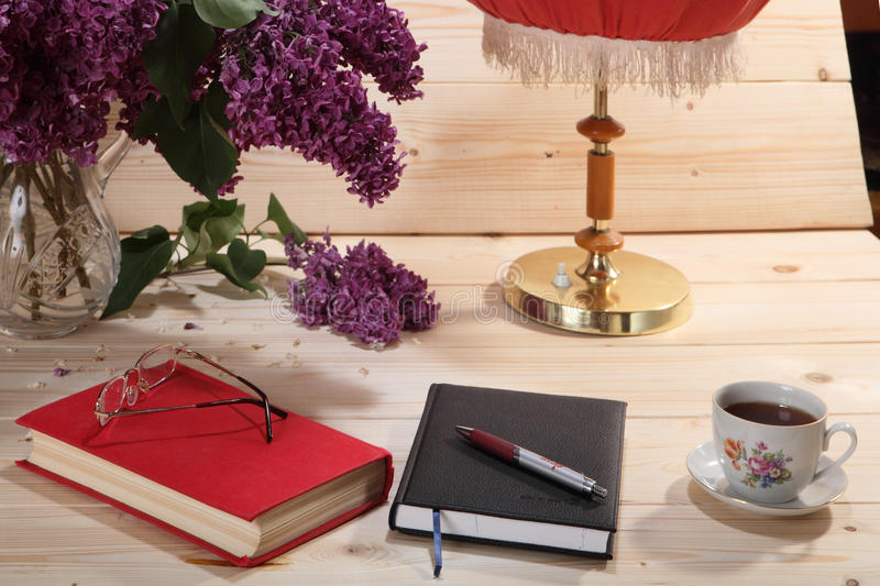 Lilas, libro, cuaderno, gafas, taza de té y lámpara de mesa foto de archivo