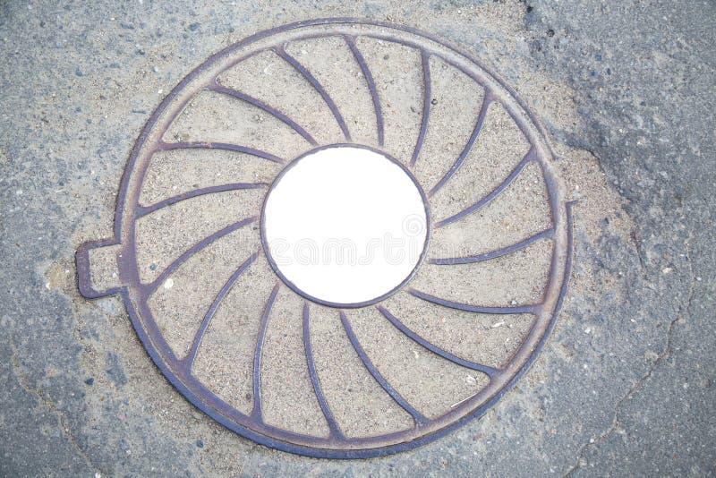 Lilas lourd de fonte de trou d'homme avec un modèle des rayons divergents sur le fond de l'asphalte gris Au centre du rond blanc photographie stock libre de droits