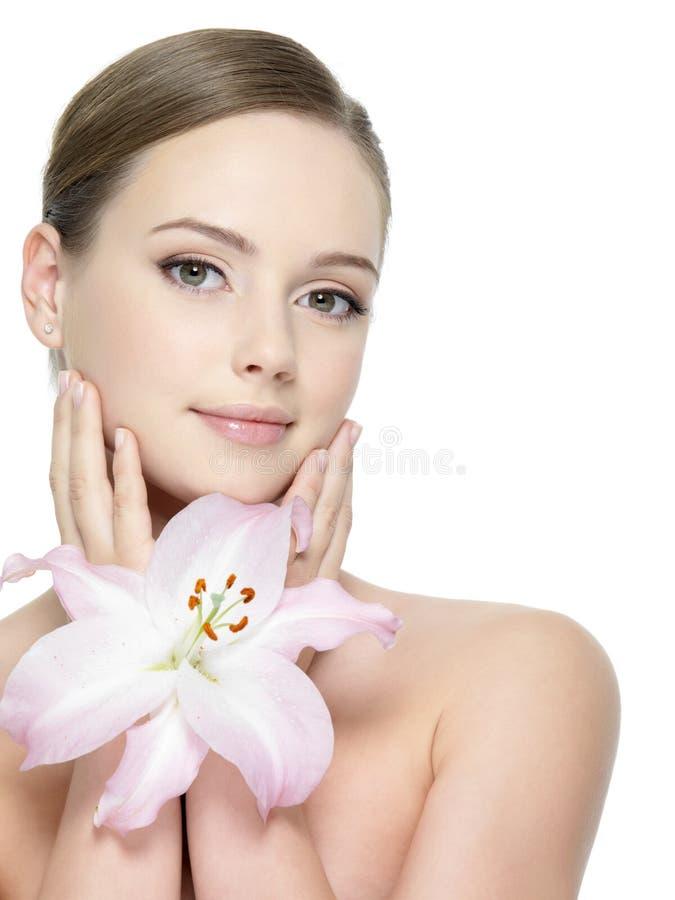Lilie nahe dem hübschen Gesicht der Frau lizenzfreie stockbilder