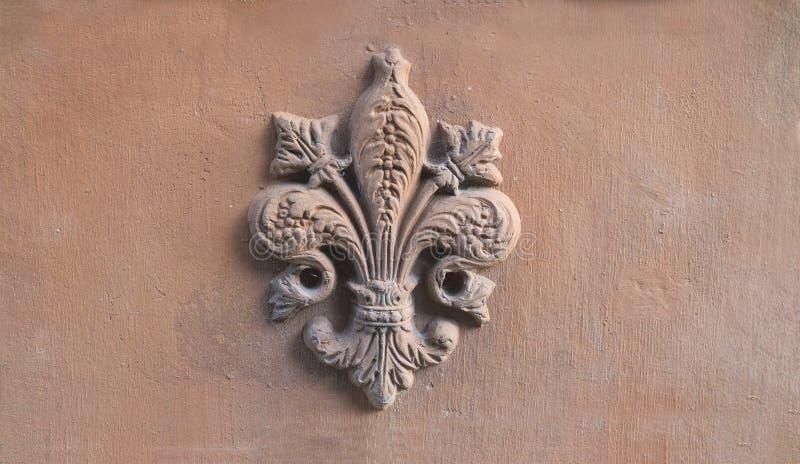 Liliensymbol von Florenz in der Entlastung auf einer alten Terrakottafliese stockfotos