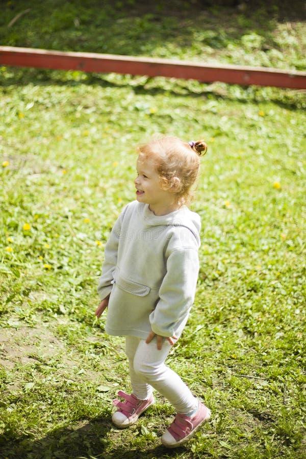 Lilittle står den lyckliga rödhåriga flickan under den härliga sommarsolen på lekplatsen arkivbild