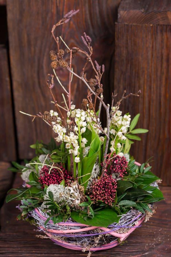 Lilja på dalen i handgjord korgdekor royaltyfri fotografi