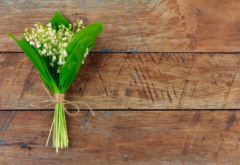 Liljekonvaljblommabuketten som binds med, tvinnar på träretro grungebakgrund royaltyfri foto