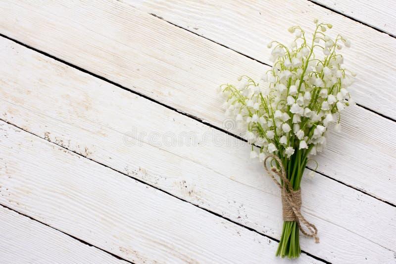 Liljekonvaljbuketten av vita blommor som binds med rad på en vit bakgrundsladugård, stiger ombord royaltyfri foto