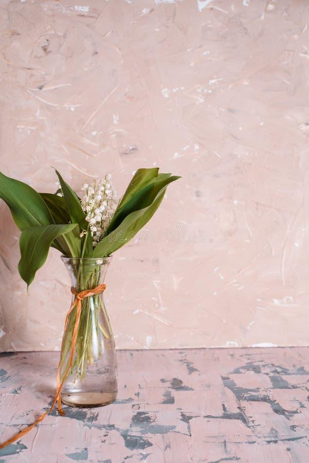 Liljekonvaljen blommar i den glass vasen, svart bakgrund, selektiv fokus royaltyfria bilder