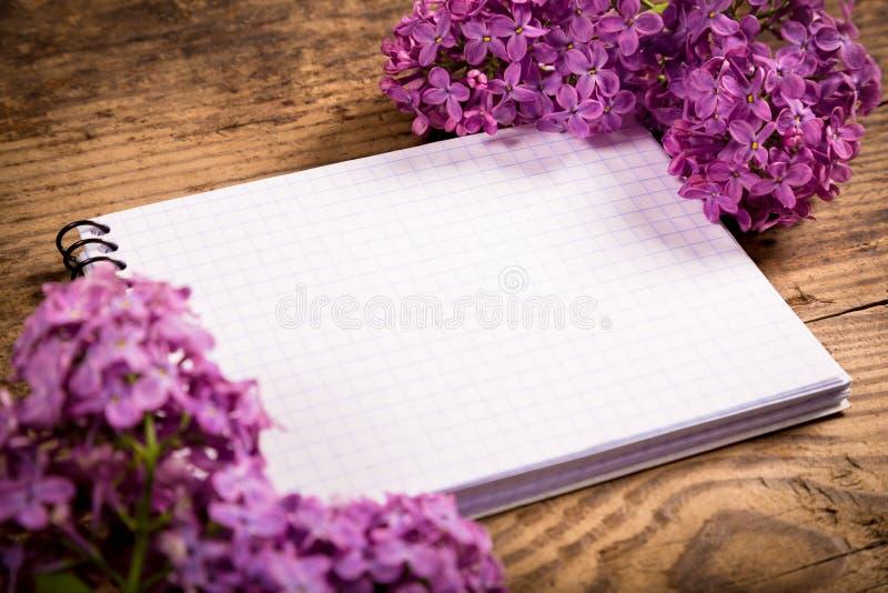 Lillà sulla vecchia tavola con il taccuino in bianco fotografie stock