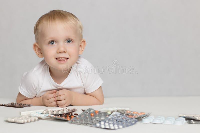 Lilla barnet behandla som ett barn på en vit bakgrund med piller och mediciner royaltyfri foto