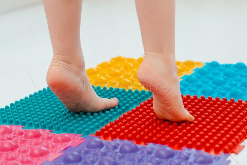 Lilla barnet behandla som ett barn p? den matta fotmassagen ?vningar f?r ben p? ortopedisk massagematta E arkivbilder