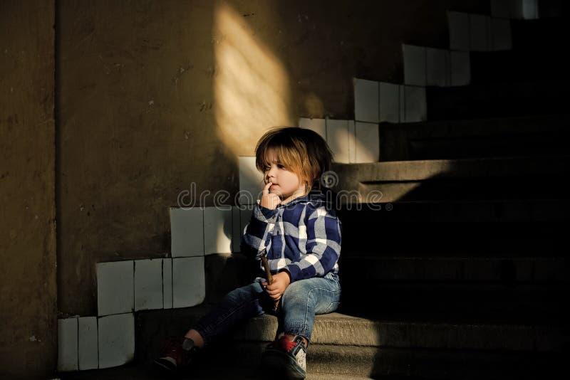 Lilla barnet med den tänkande framsidan sitter på hustrappa royaltyfria bilder