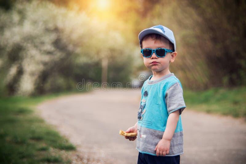 lilla barnet parkerar in och att bära solglasögon och locket royaltyfria foton