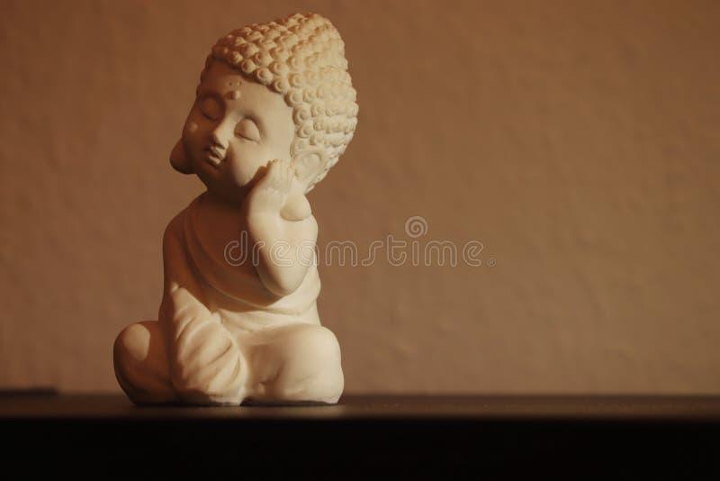 Lilla buddha som fridfullt sover i en sittande position arkivbilder