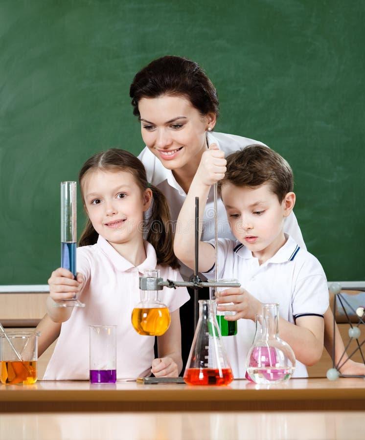 Lilla elever studerar kemi på laboratoriumgrupp arkivfoto