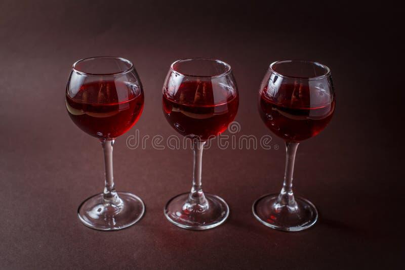 3 lilla exponeringsglas av röd starksprit på elegant mörk brun bakgrund royaltyfri bild