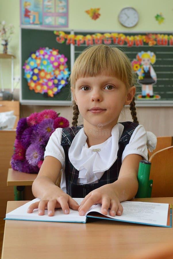 Lilla flickan är första klass på skolan royaltyfri fotografi