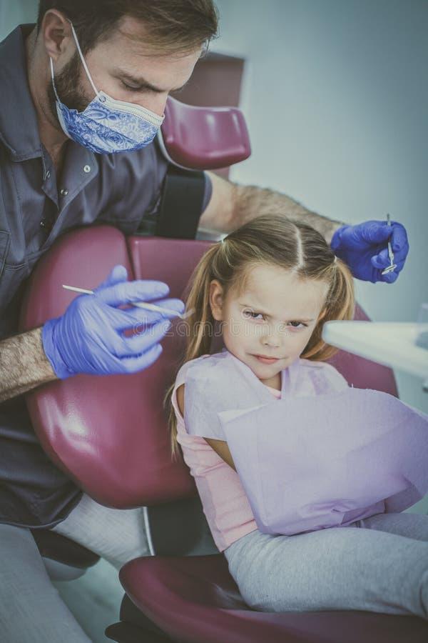 Lilla flickan är inte lycklig för tandläkareundersökning fotografering för bildbyråer