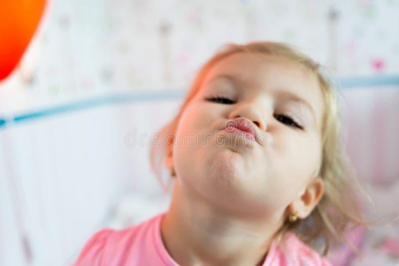 Lilla flickan är spela och le i hennes säng royaltyfri bild