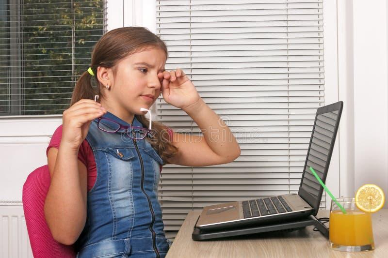 Lilla flickan är trött av att använda bärbara datorn royaltyfri bild