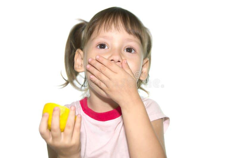 Lilla flickan äter den bittra citronen arkivbild