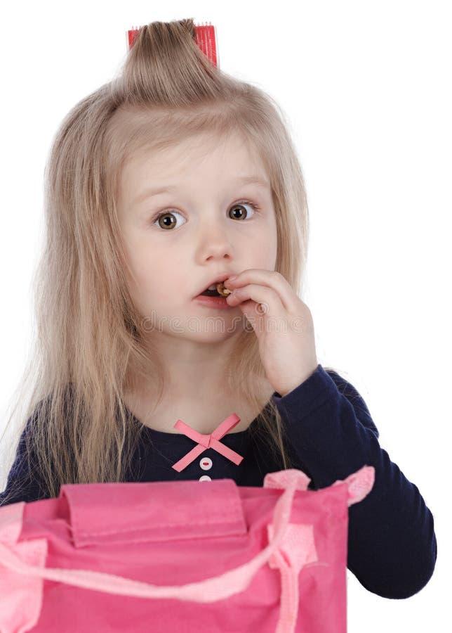 Lilla flickan äter godisen arkivfoton